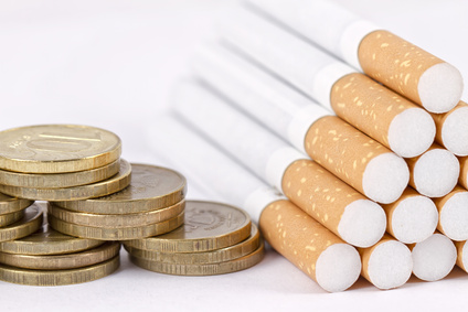 Coins lie next to a pile of cigarettes.