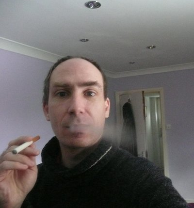 Exhaling vapour from an electronic cigarette.