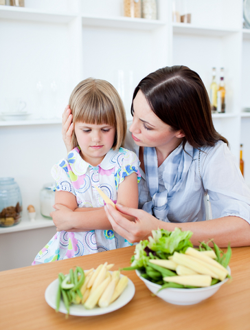 A mother showing vegetables to her daughter.