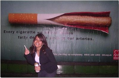A woman puffs outside a poster showing fatty deposits oozing out of a cigarette.