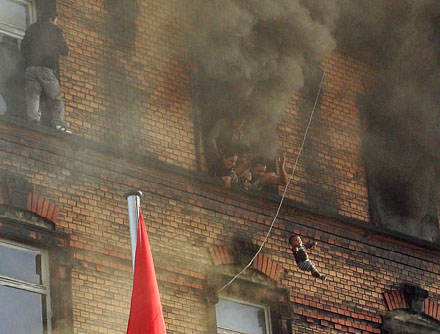A baby is thrown from a burning building.