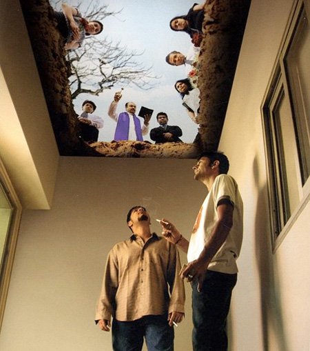 Two men smoke in a room decorated to look liike a grave.