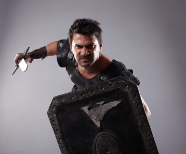 A gladiator dressed in roman clothing brandishes a sword and shield.