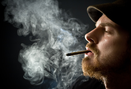 A man exhales a cloud of cigarette smoke.