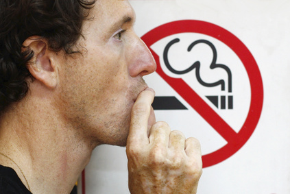 Man smoking a no-smoking sign.