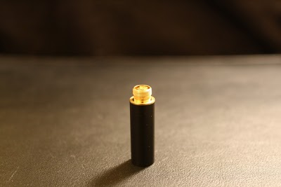 A single atomiser stands on a table top.