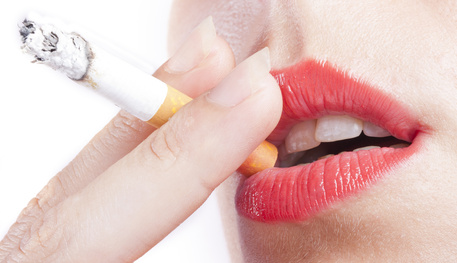 A cigarette is held to a pair of red lips.