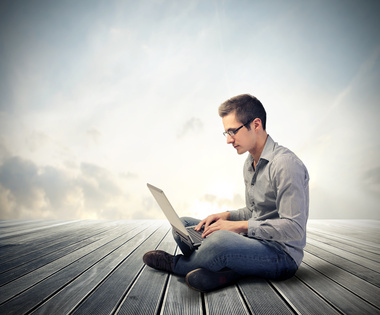 A man sits on wooden decking, clouds in the background, with a laptop on his lap.