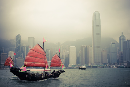 A sail boat is pictured against a Hong Kong backdrop.