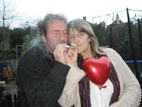 A couple enjoy their electronic cigarettes in front of a heart shaped ballon.