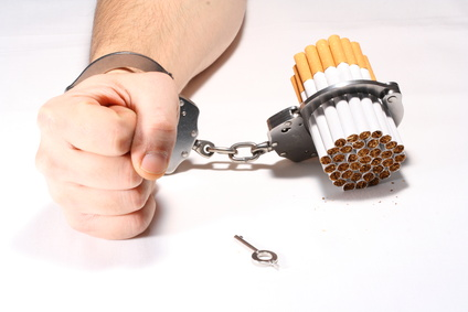 An arm is handcuffed to cigarettes.