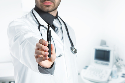 A scientist dressed in a white lab coat holds up an electronic cigarette.