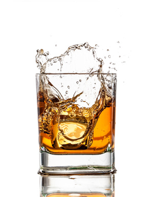 Whisky in a glass splashes into the air after ice is dropped in.