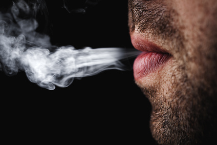 Man exhaling smoking against a dark background.