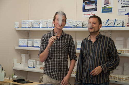 Staff exhale vapour at an electronic cigarette store.