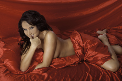 Woman lying on red satin sheets.