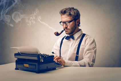 Man with pipe in bow tie in front of a type writer.