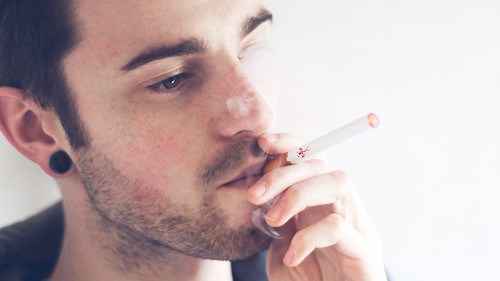 Dan inhales on an ecigarette using a regular, automatic HALO ecig battery.