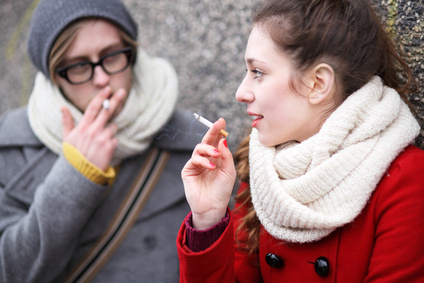 Two people smoking outside.