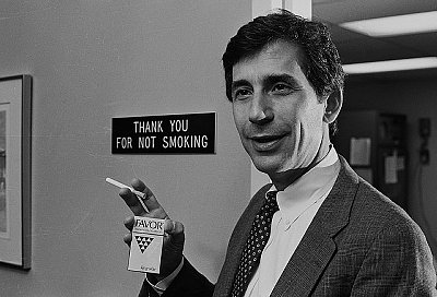 Black and white image of Dr Norman Jacobson holding the Favour cigarette.