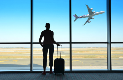 A girl stands at an airport window.