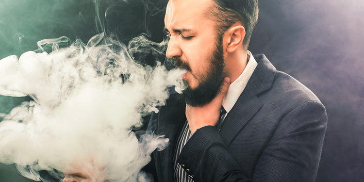 A man coughs while vaping.