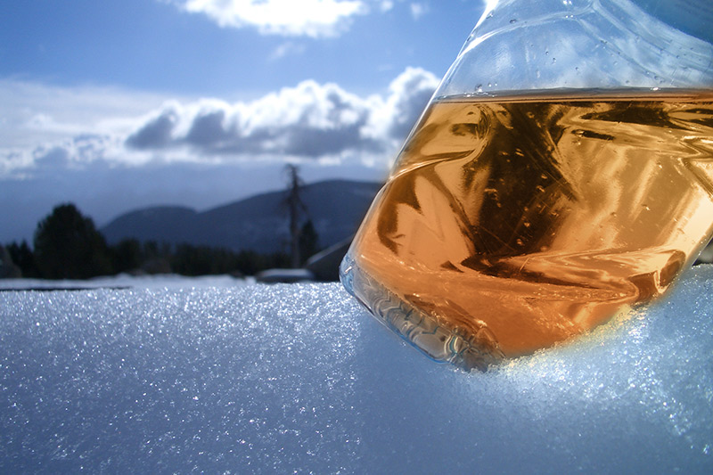 Liquid in a plastic bottle on top of a layer of snow.