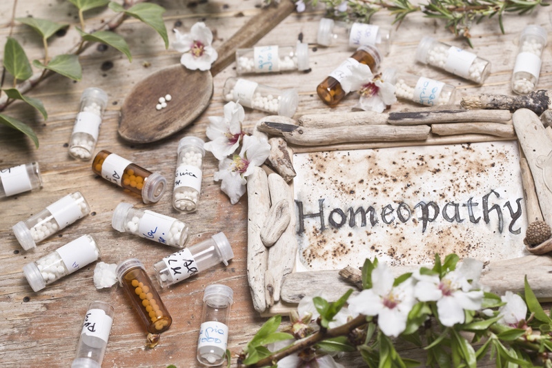 Handwritten bottles surround a sign with the word homeopathy.