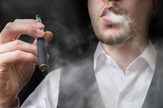 Well dressed gentleman using e-cigarette.