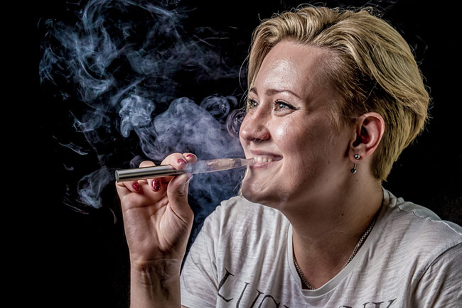 Woman vaping and smiling