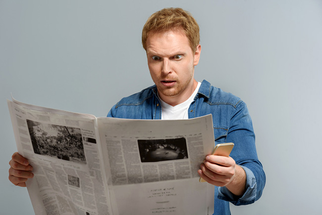Man looking shocked reading newspaper