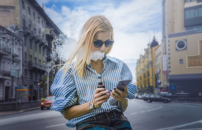 Woman on phone in the street vaping