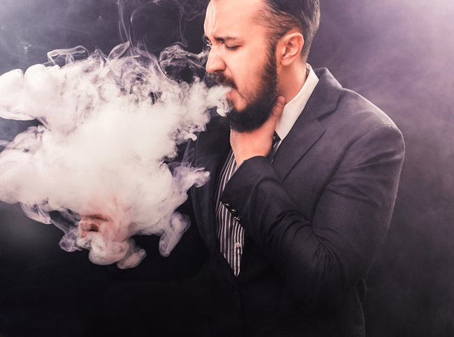 Man vaping and coughing