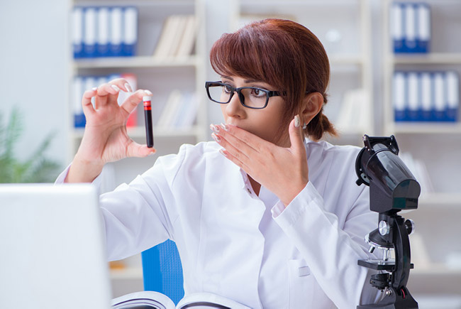 Woman in lab coat holding text tube and looking shocked.