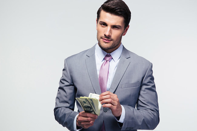Business man in suit holding a wad of cash.