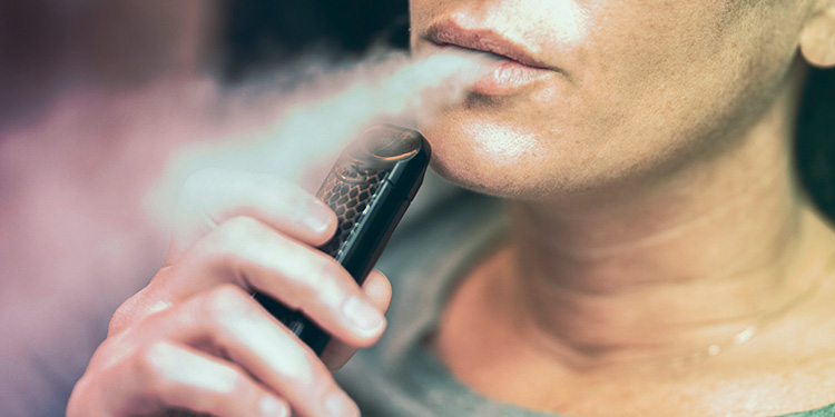 Woman vaping with a pod device.