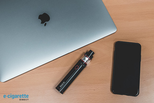 E-cig next to a laptop and a phone