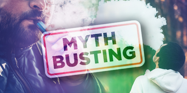 A Man vapes behind a sign saying Myth Busting.