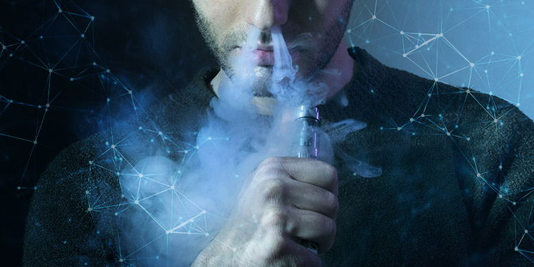 Man blowing vapour on a blue background.