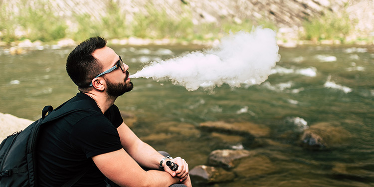 Man vaping outdoors next to a river