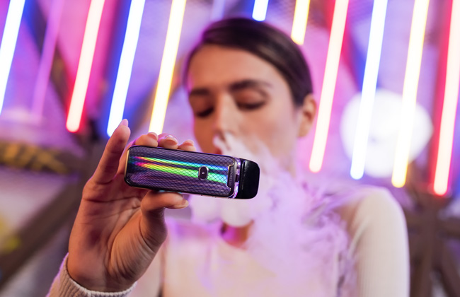 A woman exhales vapour while holding a pod system up.