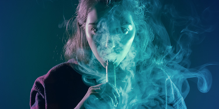 Woman vapes with her face surrounded by vapour.