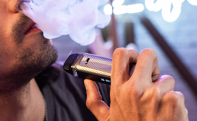 Man with stubble using a Vaporesso Luxe vape pod.