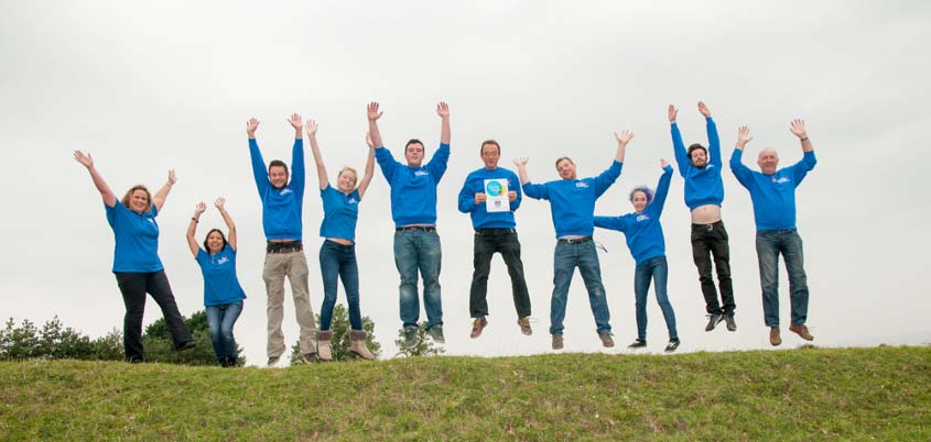 ECigaretteDirect staff jumping with the Living Wage certificate.