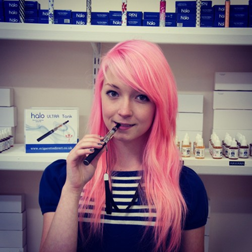 Shop staff Emily demonstrates using an electronic cigarette.